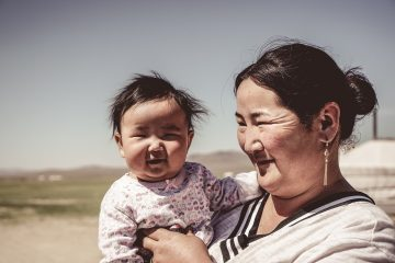 Asian mother holding baby outside.